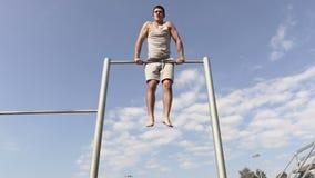 Rotación joven del atleta, practicando en barras gimnásticas almacen de metraje de vídeo