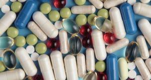 Rotación multicolora médica de las píldoras en fondo azul metrajes