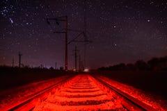 Rotaie contro il cielo stellato con illuminazione rossa insolita Fotografie Stock Libere da Diritti