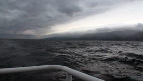 Rotaie dell'yacht su fondo delle nuvole grigio scuro in cielo e tempesta sul lago Baikal stock footage