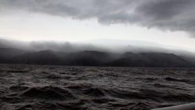 Rotaie dell'yacht su fondo delle nuvole grigio scuro in cielo e tempesta sul lago Baikal archivi video