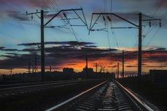 Rotaie della ferrovia che vanno per il tramonto della città Fotografia Stock