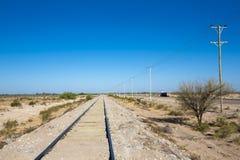 Rotaie diritte del treno nel Nord dell'Argentina con cielo blu Fotografia Stock