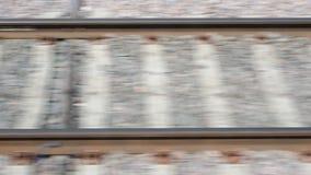 Rotaie e traversine che tremolano durante il movimento del treno Vista laterale della ferrovia dal treno veloce in città dal stock footage