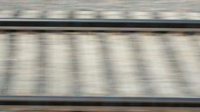 Rotaie e traversine che tremolano durante il movimento del treno Vista laterale della ferrovia dal treno veloce in città dal video d archivio