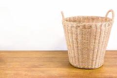 Rotanmand op houten vloer Stock Afbeeldingen
