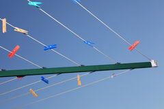 Rotary clothes dryer with pegs. Detail of an empty rotary clothes dryer with colored pegs left. Low-angle image against a blue sky royalty free stock image