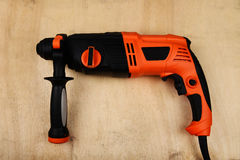 Rotary hammer. On wood background Stock Photo