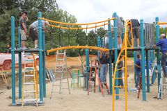 Rotary members from the community helping to build a playground for children. royalty free stock photography