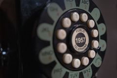Rotary of old phone in phone booth. Rotary close up of old payphone in phone booth in black, white and green-blue stock image