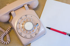 Rotary phone with blank white paper. Cream rotary retro telephone next to blank paper and pen Stock Image