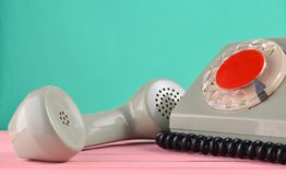 A rotary retro phone on a desk against a mint green wall.  stock photos
