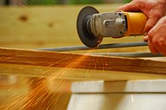 Rotary Saw and Sparks. Construction worker cutting metal rod with rotary saw creating sparks shower Stock Photo