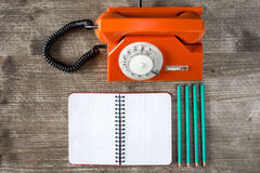 Rotary telephone, blank notebook and four pencils. Royalty Free Stock Images