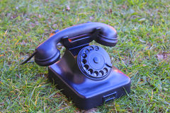 Rotary telephone in the grass. A rotary telephone in the grass Royalty Free Stock Photography
