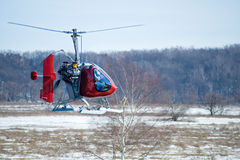 Rotary wing bird. Little red helicopter lands on a snow-covered field Stock Photo