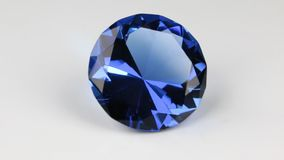 Rotate of a large blue rhinestone on a white background. Beautiful light reflection of a diamond texture. Full crystal rotation 360 degrees stock footage