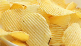 Rotate Unhealthy Harmful food, yellow delicious Potato ribbed crispy chips randomly lying on a white table background, close-up fo stock footage