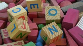 Rotating alphabetical and other toy wooden cubes. Background
