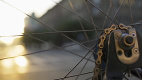 Rotating bicycle wheel closeup at city sunset. Ecological urban transport. Bike detail macro shot. Defocused city street life on background stock video