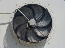 Rotating blades factory fan on the wall of the building. An external fan unit from air conditioners is attached to the facade of an industrial building. Rotating royalty free stock image