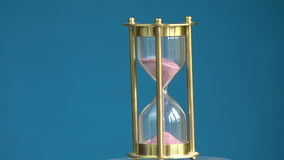 Rotating on blue background hourglass sand-glass with pink sand motion stock video footage
