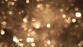 Rotating bokeh from golden tinsel. Christmas and new year background. Celebration golden light on golden backdrop stock video footage