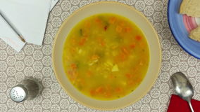 Rotating bowl of vegetable soup on the dinner table. Above shot of a rotating bowl of vegetable soup on the dinner table with a plate of bread and a spoon stock video footage