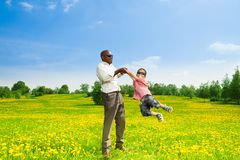 Rotating boy. Happy black father with his son rotating his boy on the field with yellow dandelions in the park Royalty Free Stock Image