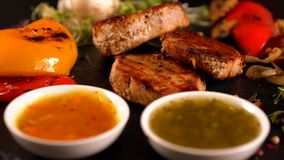 Rotating carousel with plated gourmet food. With grilled pork fillet, roasted vegetables and salad sprouts served with dipping sauces stock video