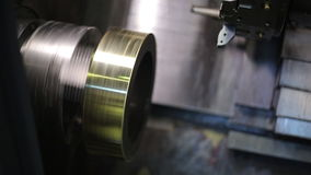 Rotating circular metal blank in a milling machine with CNC, closeup. Tightly secured with a golden shimmer, brass detail, a quick spin on spindle of automatic stock footage