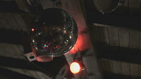Rotating disco mirror ball in dark indoors stock video