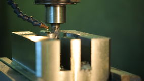Rotating a drill a vertical drill press handles metal piece with a coolant drop by drop. Amount of coolant supplied to cutting zone, varies from a few liters stock video footage