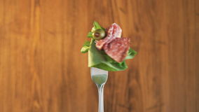 Rotating Fork With Salami and Lettuce on Wooden Background stock video footage