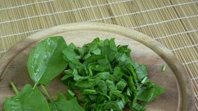 Rotating fresh chopped cutted spinach leaves on wooden chopping board stock video footage