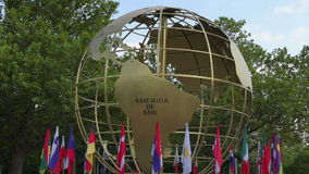 Rotating globe and flags outdoor. Maps stock video
