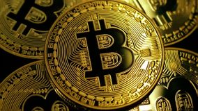 Rotating gold bitcoin. The coins are illuminated by through passing lights stock footage