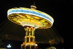 Rotating with high speed carnival attraction chain with bright l. Ights in amusement park Royalty Free Stock Photography