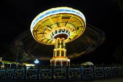 Rotating with high speed carnival attraction chain. With bright lights in amusement park Stock Image