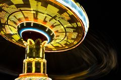 Rotating with high speed carnival attraction chain. With bright lights in amusement park Stock Images