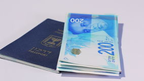 Rotating israeli money bills of 200 shekel and israeli passport stock video footage