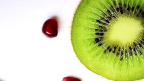 Rotating kiwi slice and pomegranate seeds, close-up. stock footage