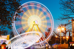 Rotating In Motion Effect Illuminated Attraction Ferris Wheel On. Rotating In Natural Motion Effect Illuminated Attraction Ferris Wheel On Summer Evening In City Stock Image