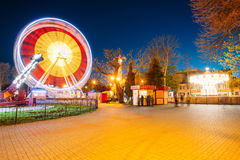 Rotating In Motion Effect Illuminated Attraction Ferris Wheel On. Rotating In Natural Motion Effect Illuminated Attraction Ferris Wheel On Summer Evening In City Royalty Free Stock Photography