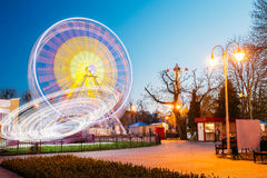 Rotating In Motion Effect Illuminated Attraction Ferris Wheel On. Rotating In Natural Motion Effect Illuminated Attraction Ferris Wheel On Summer Evening In City Royalty Free Stock Photos