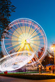Rotating In Motion Effect Illuminated Attraction Ferris Wheel. Rotating In Natural Motion Effect Illuminated Attraction Ferris Wheel On Summer Evening In City Royalty Free Stock Photography