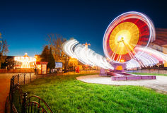 Rotating In Motion Effect Illuminated Attraction Ferris Wheel On. Rotating In Natural Motion Effect Illuminated Attraction Ferris Wheel On Summer Evening In City Royalty Free Stock Image