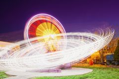 Rotating In Motion Effect Illuminated Attraction Ferris Wheel On Summer. Rotating In Natural Motion Effect Illuminated Attraction Ferris Wheel On Summer Evening Stock Photo