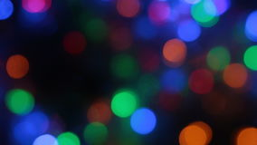 Rotating multicolored bokeh lights. Christmas and new year lights twinkling. Celebration spirit in merry flashing colorful bubbles on black backdrop stock video