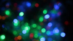 Rotating multicolored bokeh lights. Christmas and new year lights twinkling. Celebration spirit in merry flashing colorful bubbles on black backdrop stock video footage